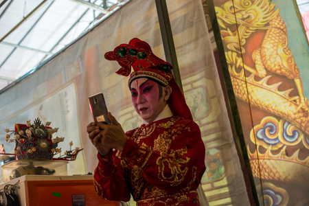 Asian Chinese male opera artiste taking selfie of himself at backstage before performing
