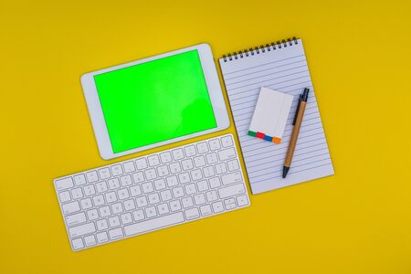Office School stationery supplies, and mobile tablet with green screen on yellow background. Business Objects Technology, flat lay concept. Stok Fotoğraf