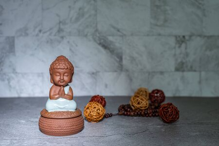Monk sitting down praying statue home decoration ornament in spotlight casting shadow. Rattan cane balls, praying beads. Empty copy space for text. Marble texture background.