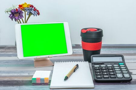 Office and school stationery supplies, reusable cup, mobile tablet with green screen. Business Objects Technology concept.