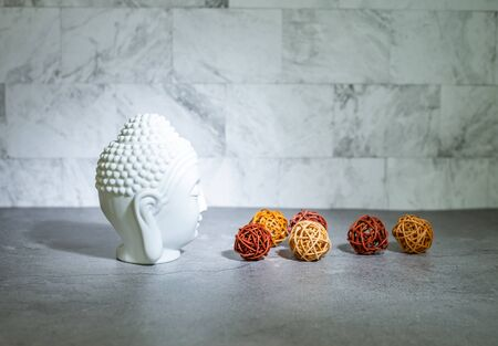 Home decoration ornament. White buddha head face, rattan cane balls. Marble texture wallpaper background concept.