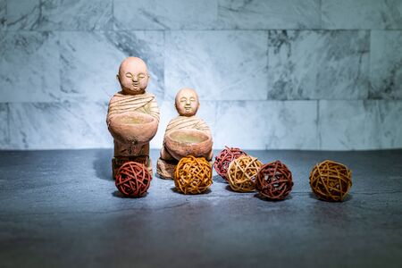 Home decoration ornament. Two little monk statue standing. Rattan cane balls. Wallpaper background. Empty copy negative space for text.