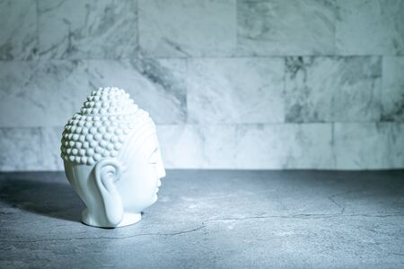 Home decoration ornament. White buddha head face. Spotlight casting shadow. Marble texture wallpaper background. Still object concept. Empty copy negative space for text. 版權商用圖片