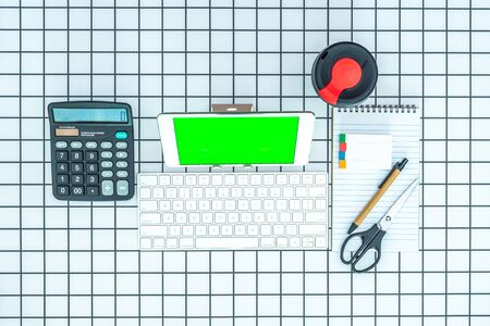 Office and school stationery supplies, reusable cup, keyboard and mobile tablet with green screen on checked background. Business Objects Technology concept. Flat lay top down. Stok Fotoğraf