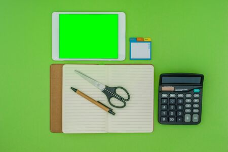 Green screen tablet, office school stationery on green background. Flat lay top down view. Business Objects Technology concept.