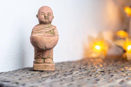 Miniature monk statue. Illuminated background. Home ornament decoration concept. Empty copy negative space for text.