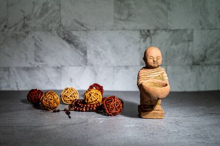 Home decoration ornament. Two little monk statue standing. Rattan cane balls, praying beads. Wallpaper background. Empty copy negative space for text. Stock fotó