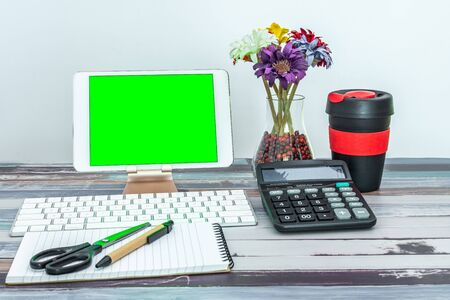 Office and school stationery supplies, reusable cup, keyboard and mobile tablet with green screen. Business Objects Technology concept.