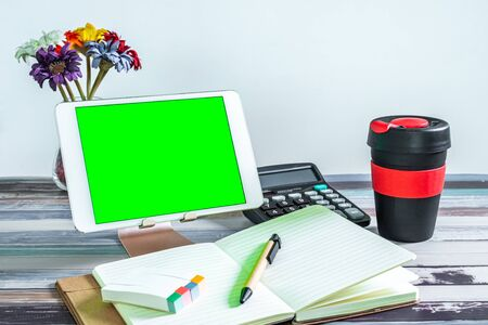 Office and school stationery supplies, reusable cup and mobile tablet with green screen. Business Objects Technology concept.