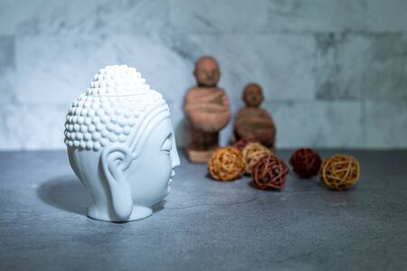 Home decoration ornament. White buddha head face, rattan cane balls. Marble texture wallpaper background concept. Empty copy negative space for text.