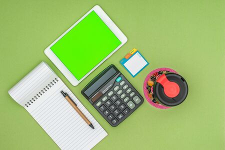 Green screen tablet, office school stationery, reusable coffee cup on green background. Flat lay top down view. Business Objects Technology concept. Stok Fotoğraf