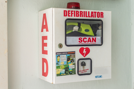 Asia / Singapore - October 10, 2019 : Automated External Defibrillator in a secured box. Medical equipment to save life in case of emergency before first responders arrive. First aid box.