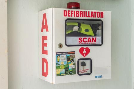 Asia / Singapur - 10 de octubre de 2019: Desfibrilador externo automatizado en una caja segura. Equipo médico para salvar vidas en caso de emergencia antes de que lleguen los socorristas. Botiquín de primeros auxilios.