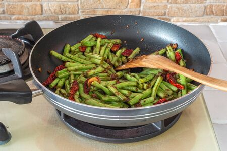 French green beans, dried chillies and garlic in stir-fry pan on cooking stove. Home kitchen food.