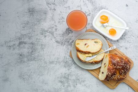 Flat lay, breakfast brunch on table. Grapefruit juice, bread, coffee and butter spread knife food drink concept.