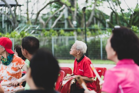 A group of seniors elderly retired active asian men women playing musical instrument singing happily enjoying life outdoor