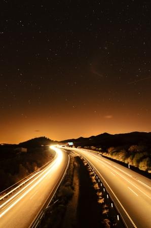 noche estrellada: tr�fico por la noche en una autopista bajo las estrellas