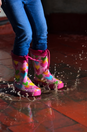 rain boots: girl jumping in the puddle with rain boots with hearts of colors