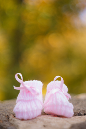 white Baby booties on a green natural background in autumn