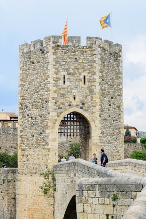 BESALU, SPAIN - AUGUST 17, 2016: People on the bridge of Besalu. The towns most significant feature,its 12th-century Romanesque bridge over the Fluvia river, which features a gateway at its midpoint.