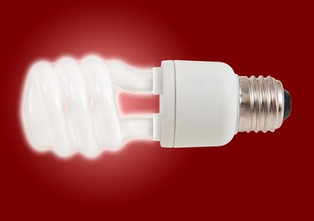 iluminate: New style light bulb glowing on red Stock Photo