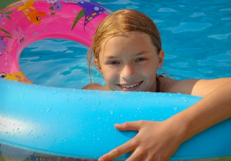 Girl in Backyard Pool in Summer photo