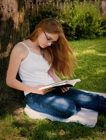 Girl Reading Book Bible Outdoors photo