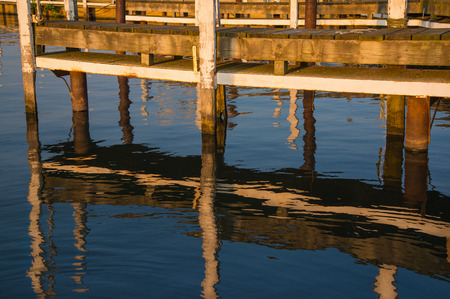 liesure: setting sun glow on old wooden dock slip Editorial