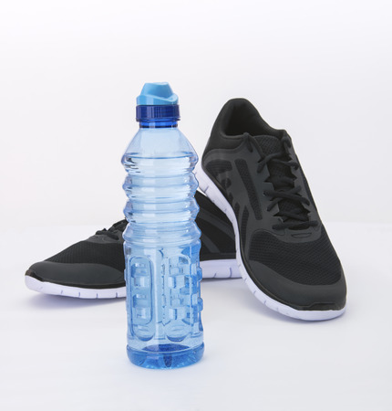 hydrate: Water bottle to hydrate runner in black shoes Stock Photo