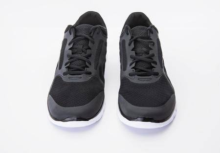 New black sports shoes on white background Фото со стока
