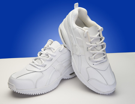 White athletic shoes with blue background