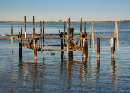 wooden dock: setting sun glow on old wooden dock slip Stock Photo