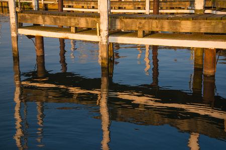liesure: setting sun glow on old wooden dock slip Stock Photo