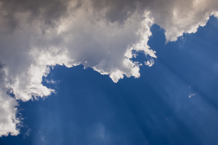 beaming: Suns rays beaming from behind clouds