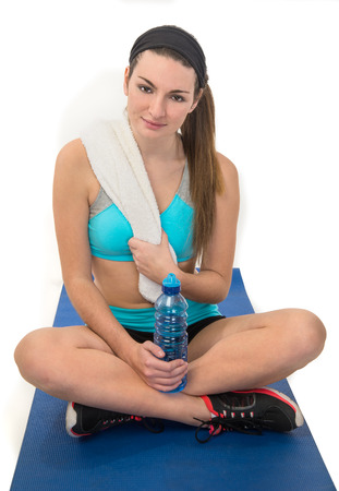 fitness female on exercise matt with water and towel Stock Photo