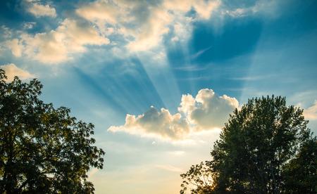 空の雲の後ろから晴れやか光線を太陽します。 写真素材