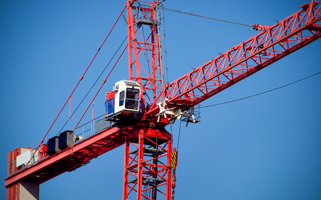 Cranes on site with boom high in sky