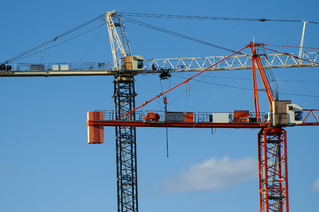 Construction cranes high on new construction project Stock Photo