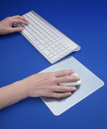 Hands on Keyboard and mouse set on blue