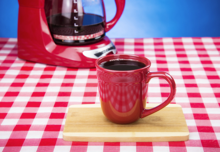 Pouring fresh Coffee red coffee maker into red cup on checkered table Stock Photo