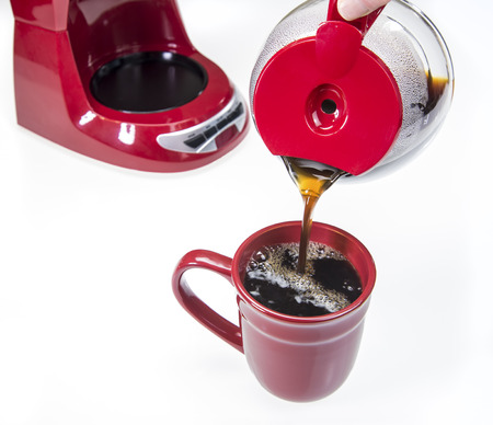 Pouring fresh Coffee red coffee maker into red cup