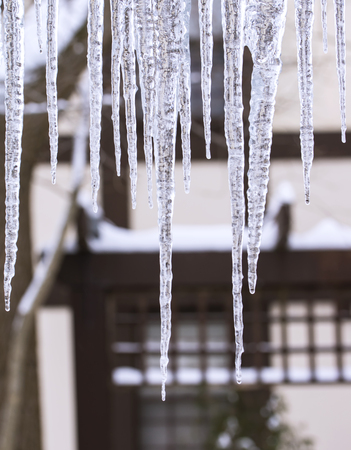 House roof eve with row of icicles hanging Stock Photo