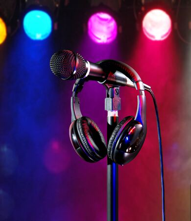 Live on colorful stage lights singers microphone and headset Foto de archivo - 138395999