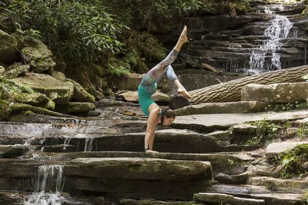 Young girl meditating with yoga in front of waterfall