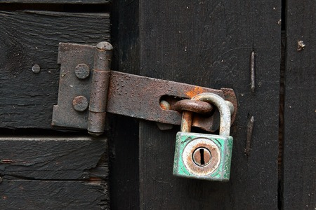 safeguarding: Padlock with an iron latch on a wooden door, detail