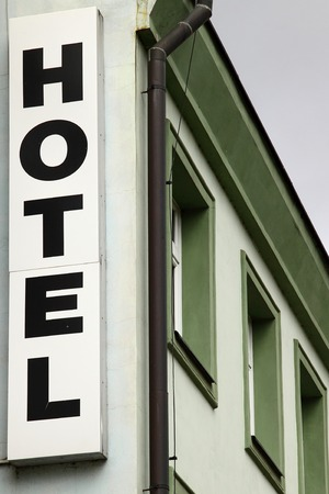 hotel sign: hotel sign, green and white hotel building in the background