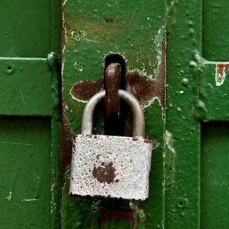 safeguards: blue, rusty, battered padlock, dark green iron gates Stock Photo