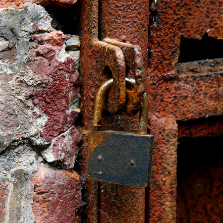 safeguarding: rusty padlock with walls and iron frame