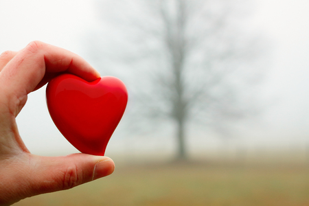 A red heart held Between the fingers