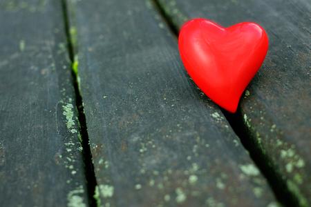 Red heart on a wooden mat